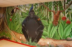 A friendly gorilla, toucan and monkey in a jungle themed playroom. The chest of the gorilla is painted with chalk board paint.