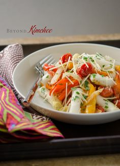Korean rice cakes are mixed with roasted mini peppers and tomatoes. It is gluten free and vegetarian!