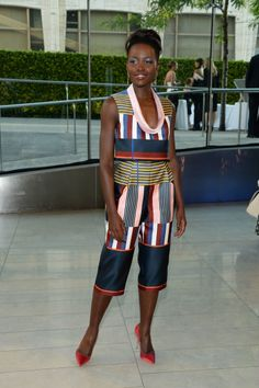Actress Lupita Nyong'o attends the 2014 CFDA Fashion Awards at Alice Tully Hall, Lincoln Center on June 2, 2014 in New York City wearing aSuno jumpsuit, in multi-colored stripes. via StyleList