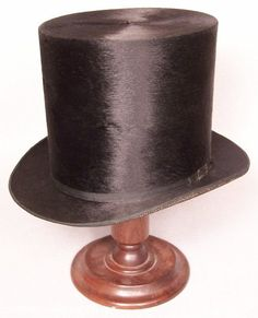 "An original circa 1860 gentleman's fine black silk plush tall hat with a tipping marking of ""QUICK, CORNING, N.Y."" for its maker Septer P. Quick, a New York born hatter and furrier... This 6 1/4"" tall hat has a slightly flared crown, a 1 3/4"" shaped brim with a ribboned edge, a narrow grosgrain ribbon hatband with bow and metal buckle, a woven silk underbrim, a 3"" deep patten leather sweatband with a laced back closure, a silk gauze faced paper lining, and the hatter's gold imprint"