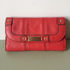 "Jessica Simpson Red Wallet Red Material. Gold Hardware. Tan Lining. Exterior has 1 Zip Pocket. Interior has 13 Card Pockets, 3 Long Slip Pockets, 1 Long Zip Pocket. Wear on all Corners and Lining is Dirty as Shown in Pictures. Measures 4""H x 6.5L x 1""D and Opens 11""H. ✅REASONABLE OFFERS NO TRADES NO PAYPAL Jessica Simpson Bags Wallets"