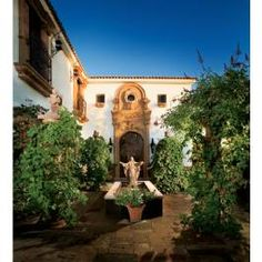 Early morning light imparts a soft glow in the grapevine-laden chapel garden at this Mesa, Ariz., residence. Behind the statue of Jesus is a home chapel.
