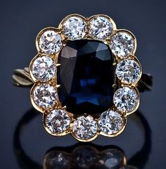 Antique  Sapphire and Diamond Engagement Ring. Russian Imperial Era Sapphire and Diamond Engagement Ring, St. Petersburg, circa 1908. A natural midnight blue sapphire in a claw setting with an approximate weight of 2.6 ct, encircled by 11 Old European cut diamonds with an approximate total weight of 2.05 carats (color F-G, average clarity VS2-SI1).