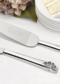 Symbolize your lives joining as you cut your wedding cake with this beautiful serving set. The silver-plated handles end in a pair of sculpted hearts. Sparkling, loose beads show through the window in the hearts for a glamorous touch. Both knife and server blades are engraved in your choice of font with two lines of personalization such as bride and groom's names on one line and wedding date on second line. Personalization will allow for up to 25 characters per line including spaces. Enter…