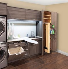 Modern laundry room features brown melamine cabinets fitted with a pull out drawer with drying rack over a pull down concealed hamper next to an enclosed stacked washer and dryer.