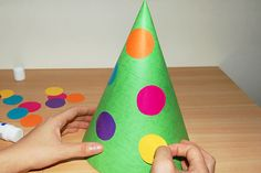 Create a cone-shaped clown hat with a fun mop of colorful curly hair made out of ribbons.