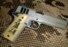 This custom 1911 was engraved on the slide as well as on the grips, which were then color-filled.