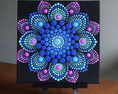 Flower burst dot mandala on black 6 x 6 canvas board blue, magenta , turquoise Excited to share this item from my shop: Flower burst dot mandala on black x canvas board blue, magenta , turquoise This beautiful representation of a mandala is an original de Mandala Painted Rocks, Mandala Rocks, Flower Mandala, Flower Art, Dot Art Painting, Stone Painting, Painting Patterns, Acrylic Painting Canvas, Mandala Design