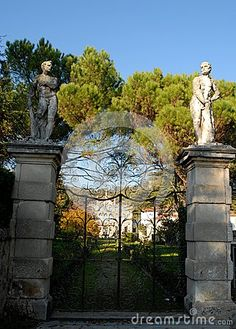 Photo taken with an elegant and beautiful villa located in the hills Hills in the province of Padua in Veneto (Italy). In the image you see the two statues that are above the two pillars that support the elegant wrought iron gate. Beyond the gate is seen at the bottom of the tree-lined facade of the villa.