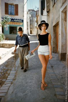Irène Gindry with newspaper in white shorts by Angelo walking down a narrow street in St. Tropez. Photo by Mark Shaw, 1961.