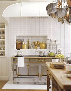 White tiled kitchen with a La Cornue range, nook above the stove for accessories