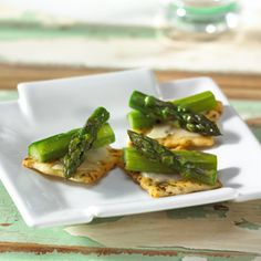 Fresh asparagus in brightly flavored vinaigrette tops the Parmesan cheese on these savory cracker appetizers.