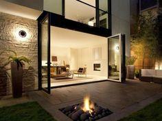 aménagement terrasse avec un foyer extérieur et beau éclairage