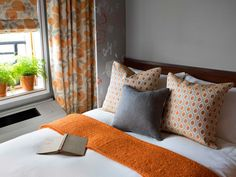 This guest room is decorated with orange and gray and has a contemporary feel.