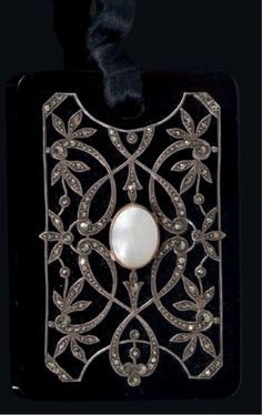 A Belle Epoque onyx and marcasite mourning pendant, French, circa 1900. The rectangular onyx plaque mounted with a foliate motif in silver and gold, centring a pearl and set with marcasites. #BelleÉpoque #mourning #pendant