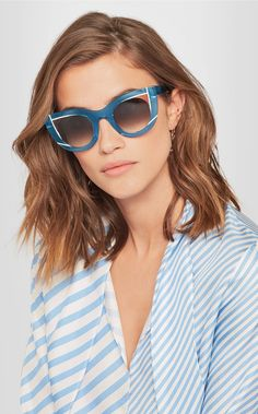 """Describing his aesthetic as """"futuristic vintage"""", Thierry Lasry is heavily influenced by the '80s and creates his own take on retro shapes. Handmade in France, these 'Wavvvy' cat-eye sunglasses are crafted from transparent blue acetate - developed by expert Italian manufacturers Mazzucchelli - and trimmed with pink and white for a more graphic look. Keep yours free from scratches in the designer-stamped hard case. https://lenshop.eu/manufacturers/13001-thierry-lasry/sunglasses"""
