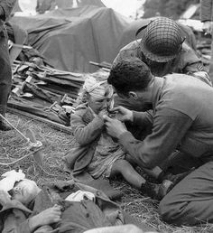 US Army medics treat and give comfort to an injured French girl, June 1944. The child was most likely caught in the crossfire of the Allies' invasion. ""