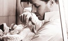 """Behind the scenes of the """"Once Upon a Time"""" pilot Josh Dallas (Prince Charming) is working his magic on baby Emma (or the baby playing baby Emma.)"""