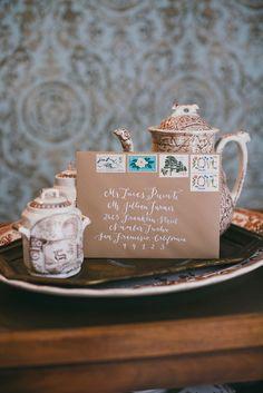white calligraphy on kraft paper, photo by Caroline Fontenot http://ruffledblog.com/rustic-chic-georgia-wedding #invitations #calligraphy