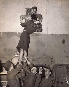 Nueva York, 1945 - La actriz Marlene Dietrich es izada para besar a un soldadoque regresa de la Segunda Guerra Mundial.