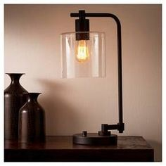 The elegance of industrial furniture shines in the Threshold Hudson Industrial Collection Desk Lamp ebony black. Utilitarian design and easygoing style radiate from this simple lamp combining a weighted base, single curved arm and a glass jar shade for a great light you'll love looking at as much as you'll appreciate its glow. Place on your home or work office desk or bedside for a simple, tasteful look in home lighting.