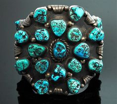 Bold and striking, this impressive vintage Navajo cuff bracelet is a true statement piece. This bracelet features twenty seven beautiful greenish blue turquoise gemstones in an unusual handmade sterling silver setting. This stunning piece would work well for both men and women. Vintage Navajo Sterling silver Turquoise Dimensions: 3 1/4 wide and 2 1/2 across Inside measures approximately 5, gap measures just over 1.5.