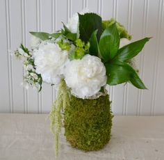 sheet moss wrapped around a mason jar -- secured with floral wire.  What an organic container for your flowers...