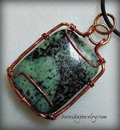 A rectangular green stone with black matrix (possibly a type of Jasper) is simply wrapped in hammered copper.  Brass jump rings at the top make it easy to hang this pendant from almost any size cord o