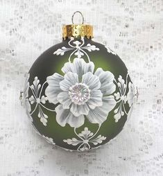 Margot Clark created this soft olive colored glass ornament with White 3D texture painted MUD floral design with added bling centers. Each