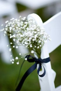 baby's breath tied to chairs with ribbon