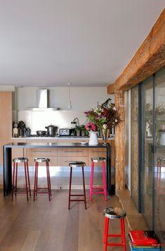 Rien de tel que des tabourets colorés rose et rouge flash pour donner du pep's à une cuisine en bois (Source Côté Maison)
