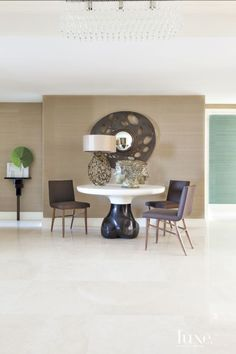 The entry gathers an Eric Schmitt table, a Hervé Van der Straeten lamp and mirror, and Patrick Naggar chairs, all from Ralph Pucci International. Holland & Sherry wallpaper wraps the space, and Axel Salto's Janus Head for Royal Copenhagen, from Bernd Goeckler Antiques in New York, holds court.