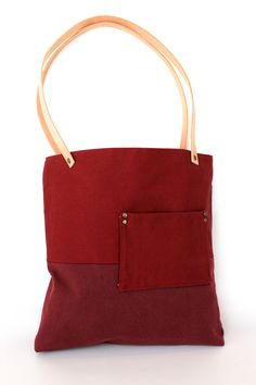 half off sale!  regular price $61, sale price $30.50  Red brick duck cloth and burgundy canvas exterior with small front side pocket. Veg tanned raw leather straps with antique brass rivets, tea stained muslin lining with burgundy cotton slip pocket, magnetic snap closure.