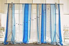 Ah, something blue: a cooling, calming color to soothe your wedding day nerves. This particular backdrop is reminiscent of the ocean and is a welcome change of pace from the traditional neutral color palette. The birds are a whimsical addition. Any color works, use fabric or drapery panels, fabric can be cut longer though