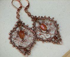 The warm beauty of antiqued copper combines with fiery sunstone in these very feminine handmade wire wrapped earrings from Owl Hollow Studio. The artisan original earrings each have a framed fili