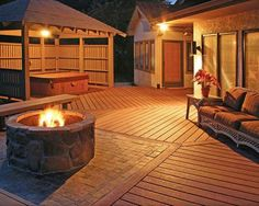 A large deck with fire pit and covered hot tub and privacy fence.