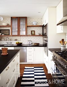 Walnut open shelving and glass-fronted cabinets make the kitchen feel more expansive. Subway tile with dark grout lends the room a bistro-inspired feel. | Design: Barbara Purdy | Photo: Angus Fergusson