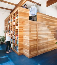 a completely customized 16-by-17-by-10-foot wooden box that accommodates a bookcase on the outside, a bedroom on the inside, and a dressing-room mezzanine above.