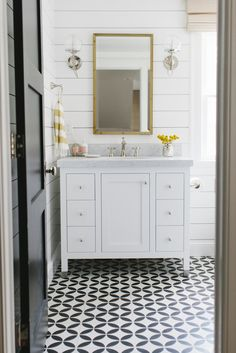 lovely bathroom with small white vanity | shiplap | cool sconces | beautiful black and white encaustic tiled floor | black door | sophisticated country design