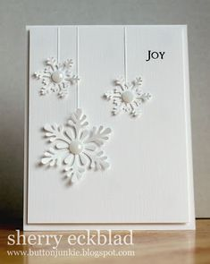 handmade card from the button junkie: snowflakes ... white on white ... clean and simple ... three die cut snowflakes hanging on strings ... delightful!!