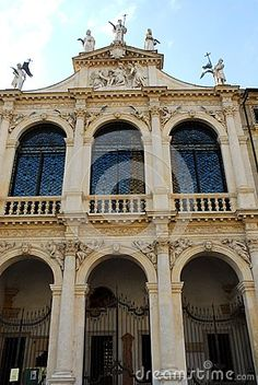 Photo taken at pawnshop in Vicenza in Veneto (Italy). In the image, the Piazza resumption of Gentlemen we see the beautiful facade exposed to the south of the historic building. Particularly beautiful are the three large arched windows that are above the three large arches on the ground floor of the porch. Above the roof statues they rise in the blue sky.