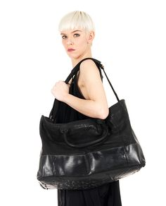 O.X.S. RUBBER SOUL Black perforated leather tote bag with leather handles adjustable and removable shoulder strap one inner zippered pocket rubber layer on the lower part top zipper closure