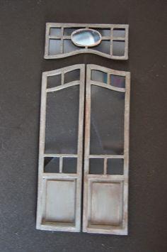Réalisée en bois et en carton, un carreau de cette grande porte intérieure usée par le temps est cassé, un autre de ses vitres est fen...