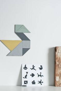 wooden tangram magnet set Tangram is a Chinese tile-based game which makes it possible to position the pieces into more than 1000 images/shapes/designs Due to their magnetic abilities you can put up shapes and new designs on your fridge. The set consists of seven pieces which range from grey, light green to mint color. They are made of wood (2mm), varnished on the front side (colors grey, light green and mint) and covered with a magnetic film on the back. Additionally you will get ...