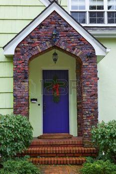 purple door: Multi-color Klinker brick borders a purple door of a yellow home