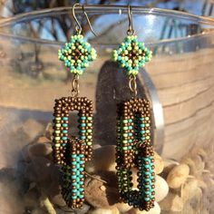 Matte Bronze Dual Link Earrings designed by the Navajo sister and brother team TSOul. Made with size 11 seed beads in matte bronze, sea foam green & turquoise blue seed beads as well as a beaded enclosed tribal diamond atop the dual links. Shown at Beyond Buckskin Boutique