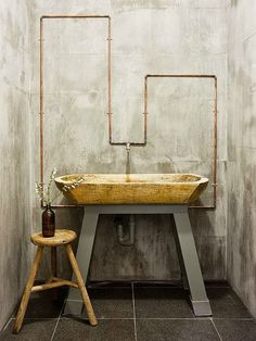 simple bathroom. wood sink exposed pipes. concrete. beauty