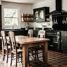 Black painted cupboards and red and black tiled floor make for a dramatic combination in this kitchen by Plain English's diffusion range British Standard.