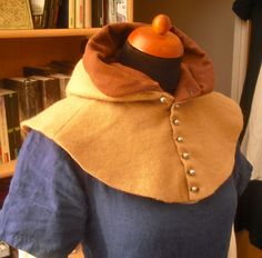 Buttoned hood (14th century) made of light brown wool and auburn linen, with pewter buttons.