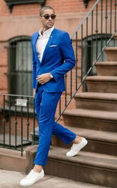 costard homme, costume bleu roi, chemise blanche, baskets blanches, lunettes de soleil Ray Ban, mouchoir de poche blanc discret